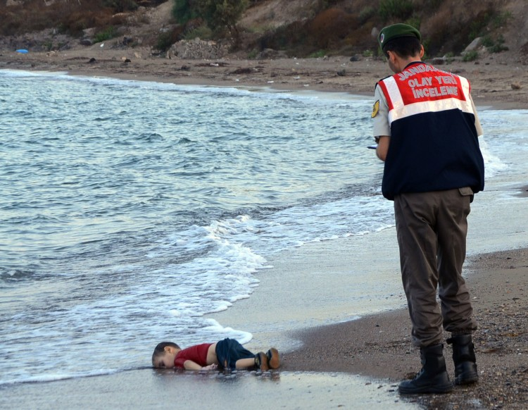 FILE - In this September 2, 2015 file photo, a paramilitary police officer investigates the scene before carrying the lifeless body of 3-year-old Aylan Kurdi from the sea shore, near the beach resort of Bodrum, Turkey. Turkey's state-run news agency said Friday March 4, 2016 a court has sentenced two Syrian smugglers to four years and two months each in prison over the death of 3-year-old migrant boy Aylan Kurdi and four other people. (AP Photo/Nilufer Demir, DHA, File) TURKEY OUT ORG XMIT: LON801